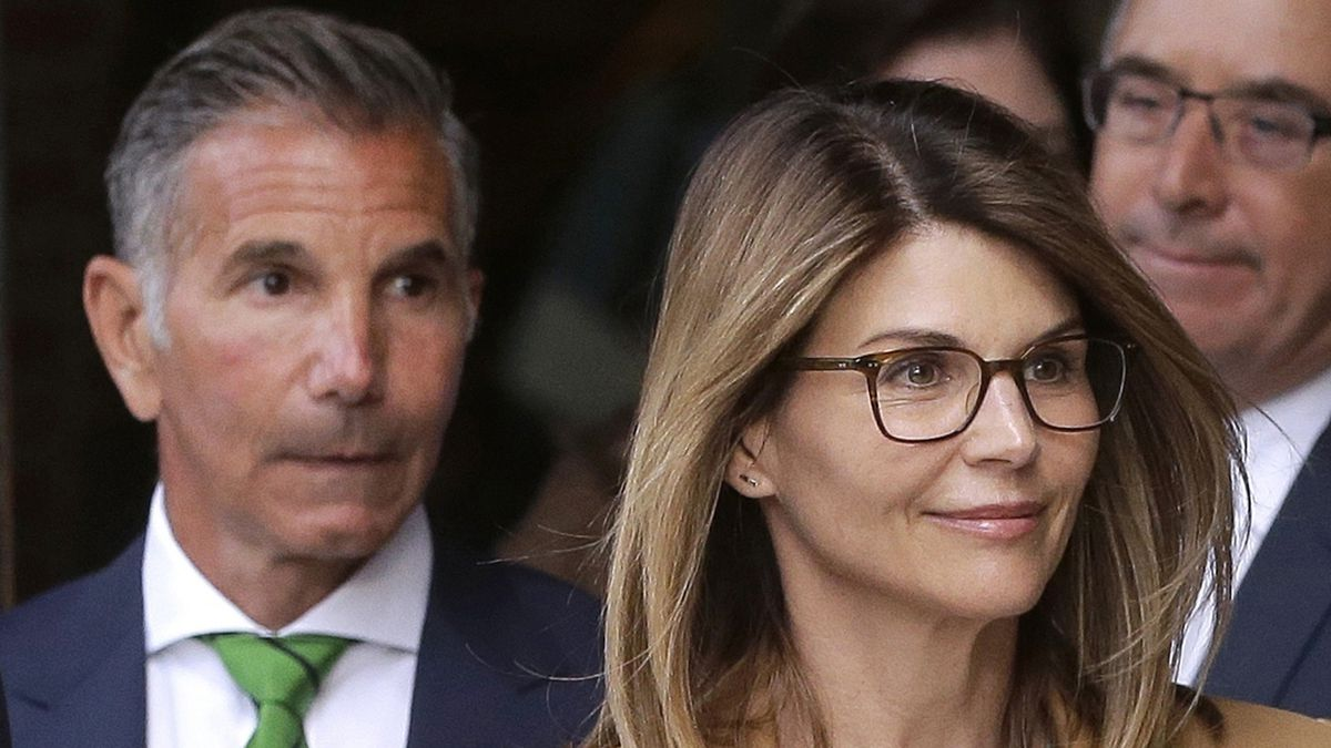 In this April 3, 2019, file photo, actress Lori Loughlin, front, and her husband, clothing designer Mossimo Giannulli, left, depart federal court in Boston after a hearing in a nationwide college admissions bribery scandal. In a court filing on Monday, July 13, 2020, lawyers for the couple, who admitted to paying $500,000 to get their daughters into the University of Southern California as fake crew recruits, asked a judge to lower their bail from $1 million to $100,000, saying they will not flee ahead of their August sentencing in the college admissions bribery case.
