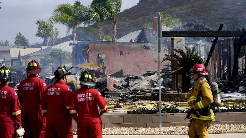 Fire crews work the scene of a small plane crash, Monday, Oct. 11, 2021, in Santee, Calif. At...