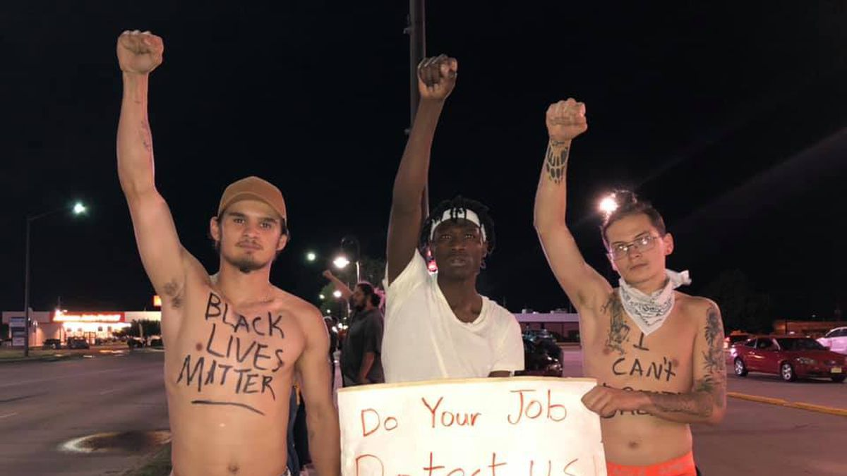 Three protest organizers hold a sign against police brutality during the second straight night of protests in Grand Island. (Credit: Kelsey Dickeson, KSNB)