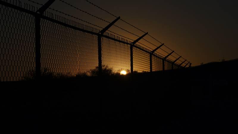 The sun sets behind a border fence separating Del Rio, Texas, and Ciudad Acuna, Mexico,...