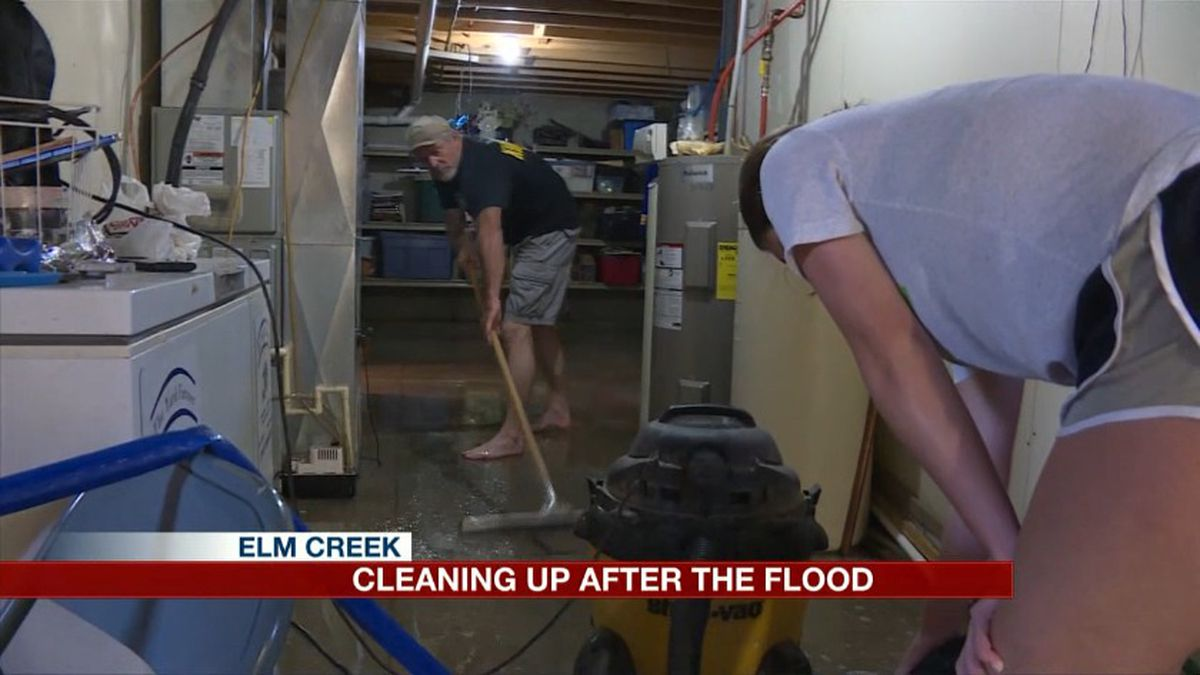 The Brown family cleans up three inches of water in their basement Tuesday after Monday night storms flooded their downstairs area. (Source: Kelsey Dickeson, KSNB)