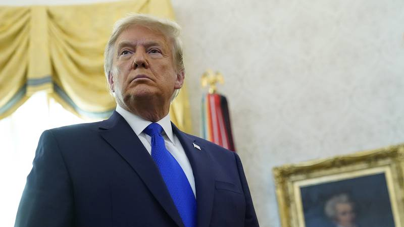 President Donald Trump listens to a reporter's question after awarding the Presidential Medal...