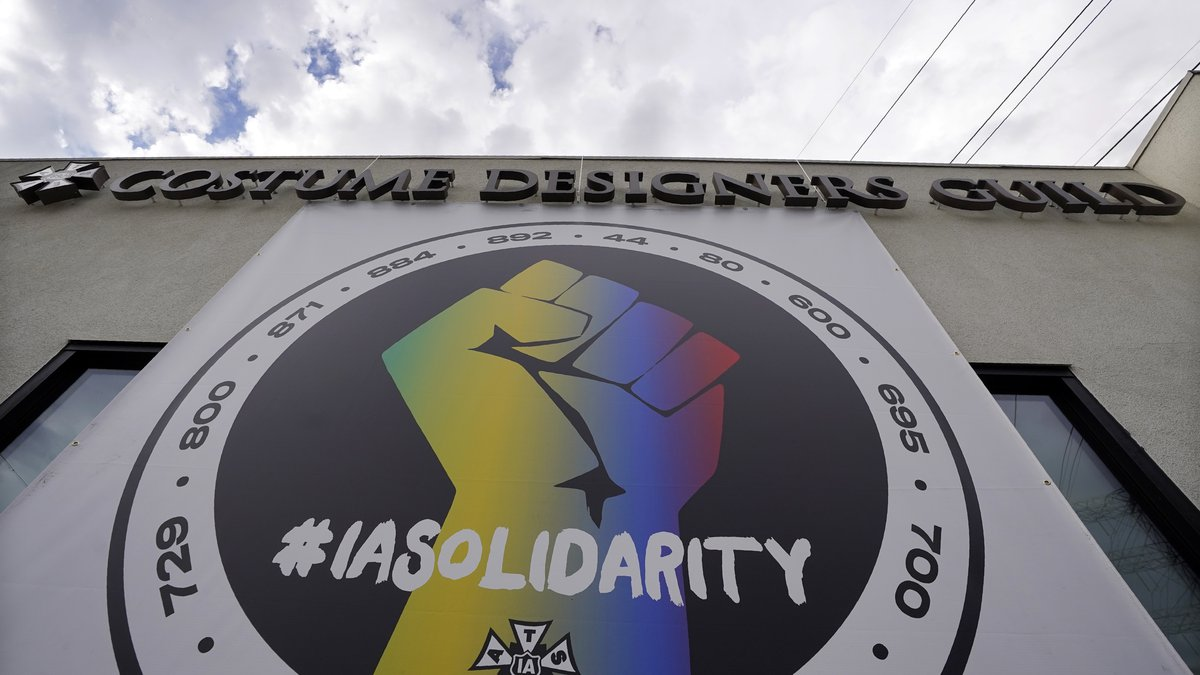 A poster advocating union solidarity hangs from a Costume Designers Guild office building,...