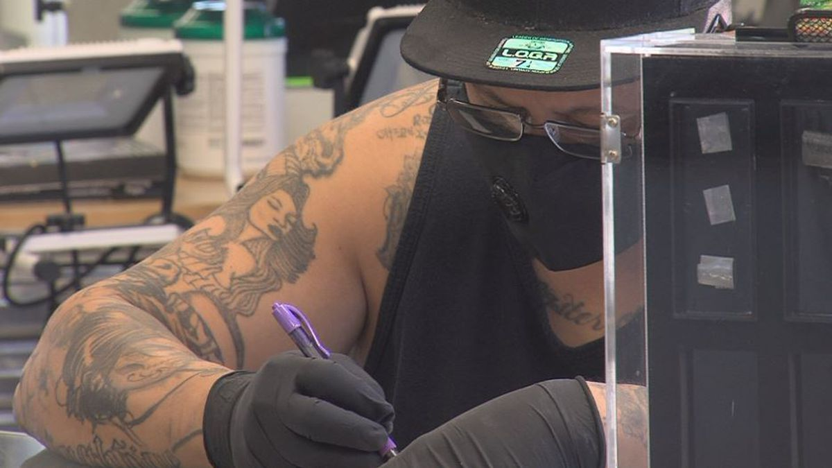 A tattoo artist works on a design on his first day back to work after the pandemic. (Credit: Alicia Naspretto, KSNB)
