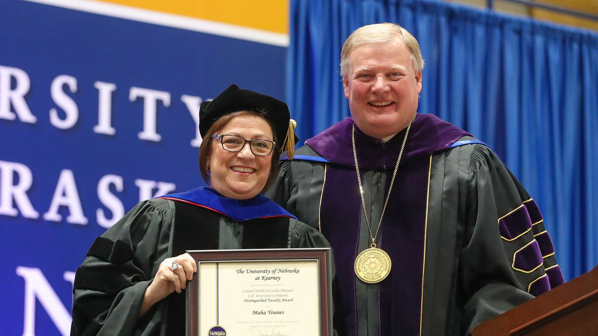 Maha Younes, a professor in UNK's Department of Social Work, receives the Leland Holdt/Security Mutual Life Insurance Company Distinguished Faculty Award from Chancellor Doug Kristensen during Friday's winter commencement at the Health and Sports Center. (Photo by Corbey R. Dorsey, UNK Communications)