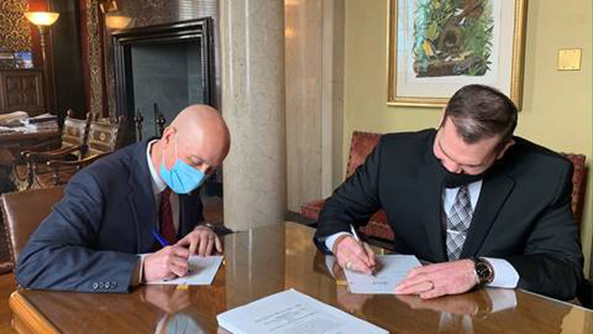 Gov. Ricketts (left) and the State's Chief Human Resources Officer, Jason Jackson (right), sign...
