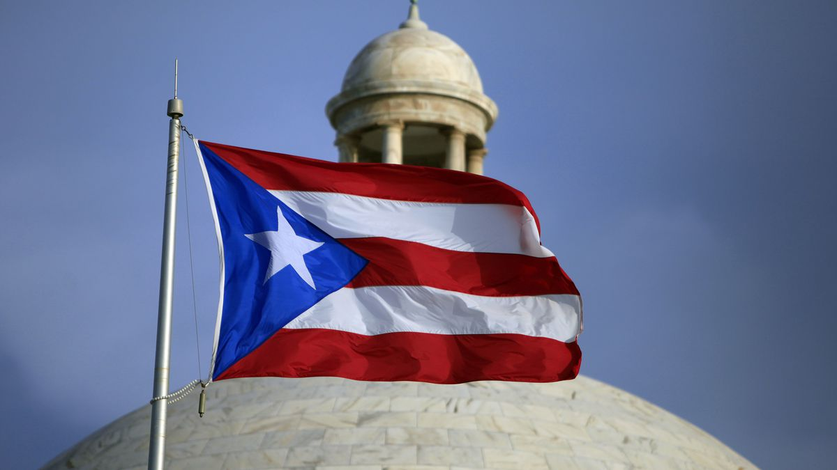 FILE - In this July 29, file 2015 photo, the Puerto Rican flag flies in front of Puerto Rico's Capitol as in San Juan, Puerto Rico.  (AP Photo/Ricardo Arduengo, File)