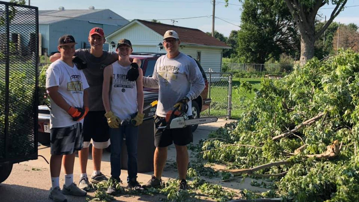 Northwest High School football players post with their coach next to tree debris they helped...