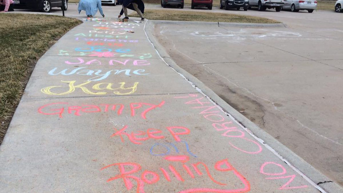People wrote chalk messages to family members quarantined inside The Heritage at Sagewood...