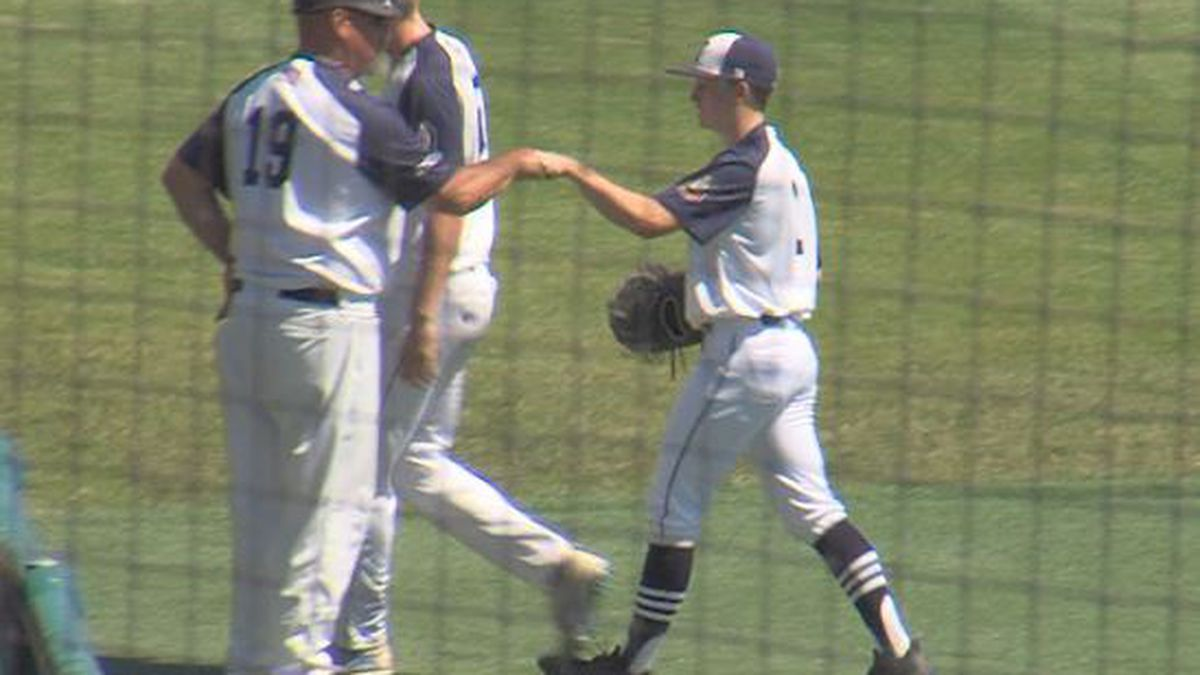 Coach Brad Archer gives Sam Engberg a fist bump after a diving catch in the fourth inning.