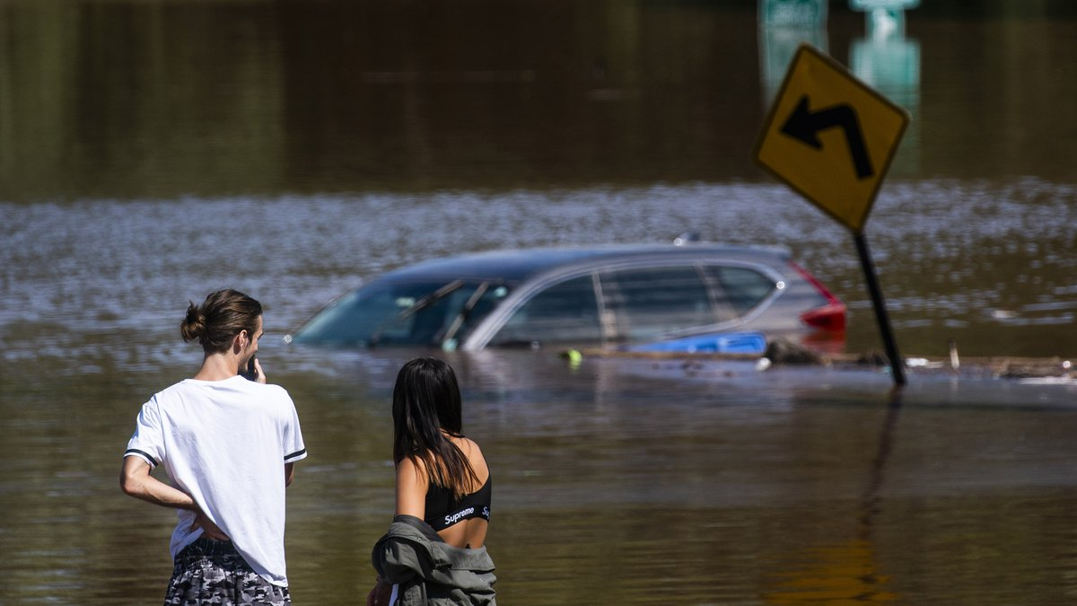 People look at a car flooded flooded as a result of the remnants of Hurricane Ida in a local...