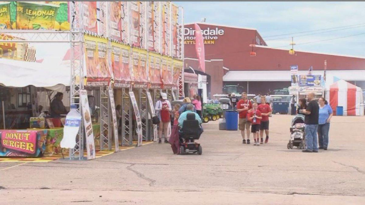 State Fair goers walk through food vendors, enjoying a nice day at Fonner Park. (Credit: Alicia...