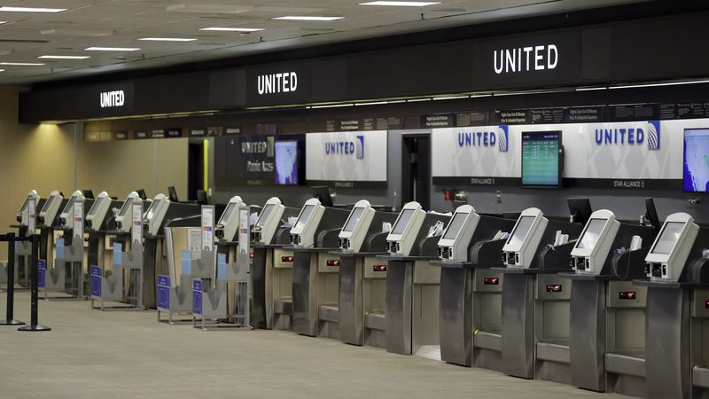 FILE - In this April 24, 2020 file photo, empty United Airlines ticket machines are shown at...