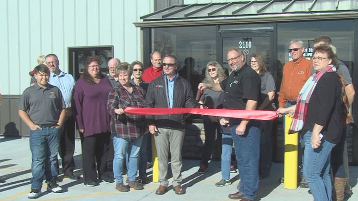 Family members and company employees stand together as presidents cut ribbon. (Credit: Alicia Naspretto, KSNB)