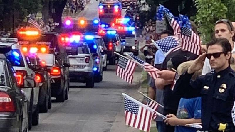 A uniformed officer gives a salute as the motorcade in front of the hearse carrying...