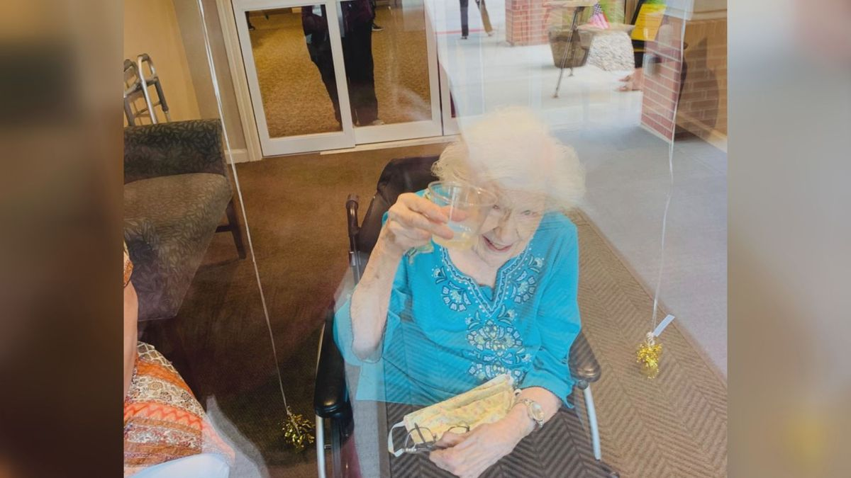Elsie Steinauer raises a toast to 106 years. She was watching people parade past her long-term care facility.