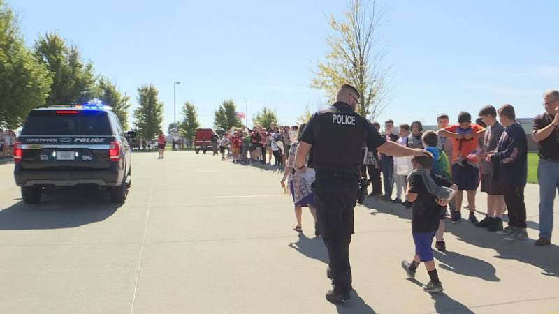 Brad Cunningham walks alongside his son as the middle schoolers, first responders and law...