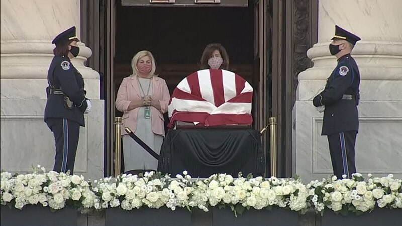 Mourners stand outside the Capitol in Washington, D.C. to pay their final respects to the late...