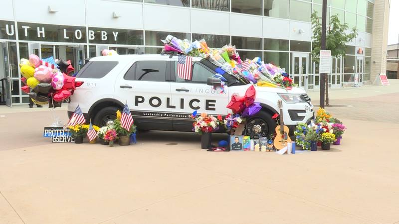 Herrera's cruiser parked outside PBA covered in flowers, thank you notes and other rosaries