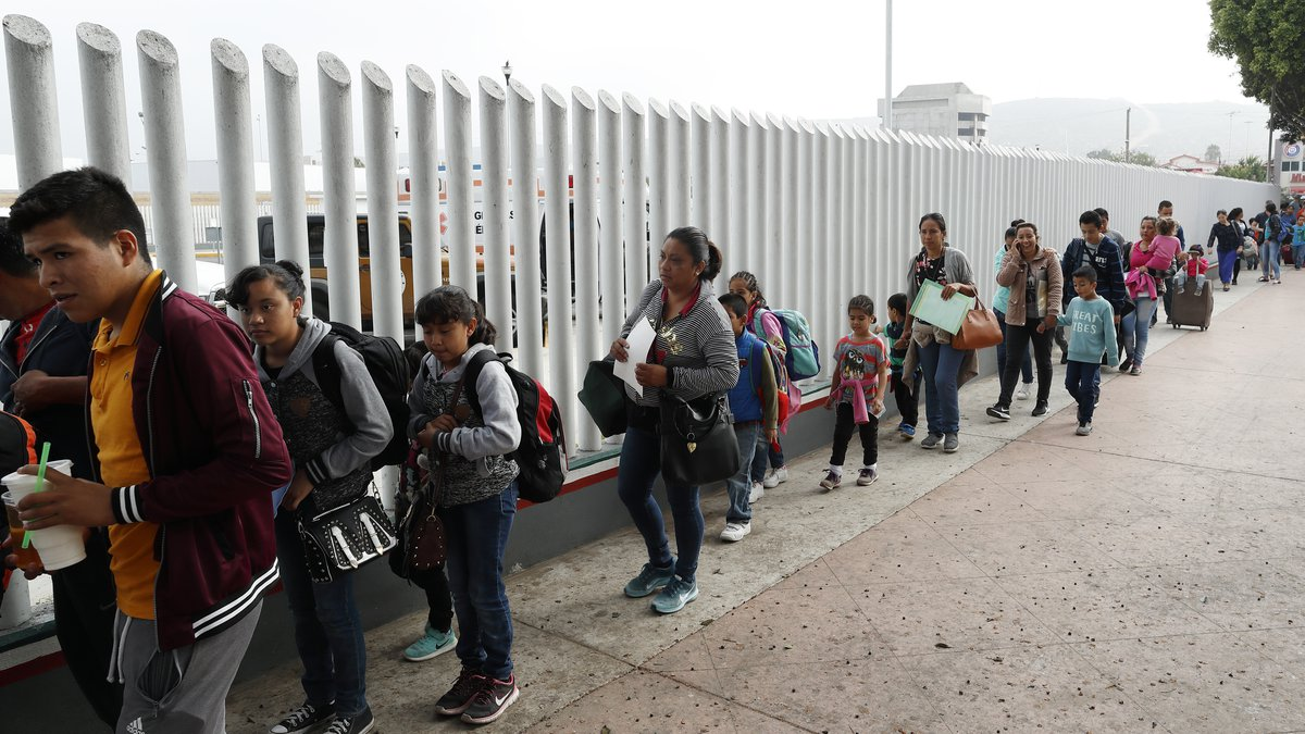 This July 26, 2018, file photo shows people lining up to cross into the United States to begin...
