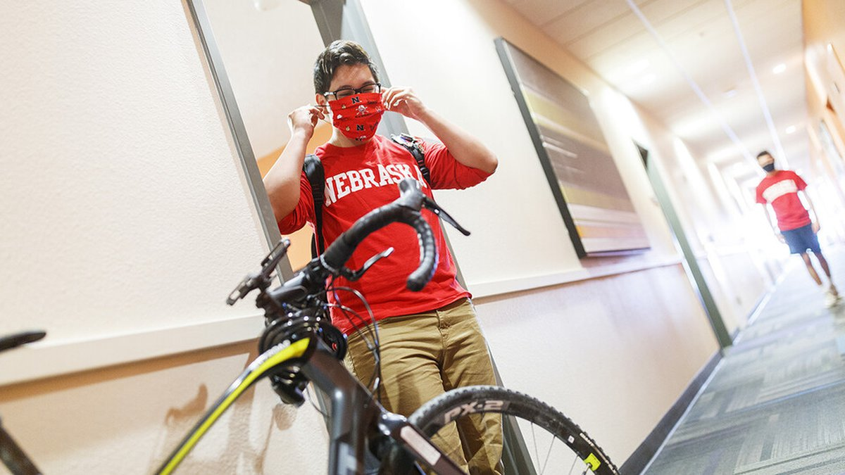 PJ Miguelino puts on his mask as he leaves a Suites Residence Hall room.