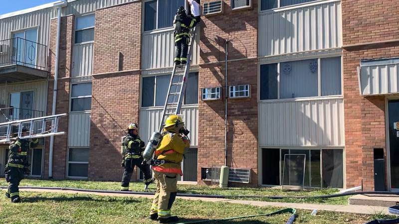 A person is being helped down the ladder by a Hastings firefighter as crews work to control a...