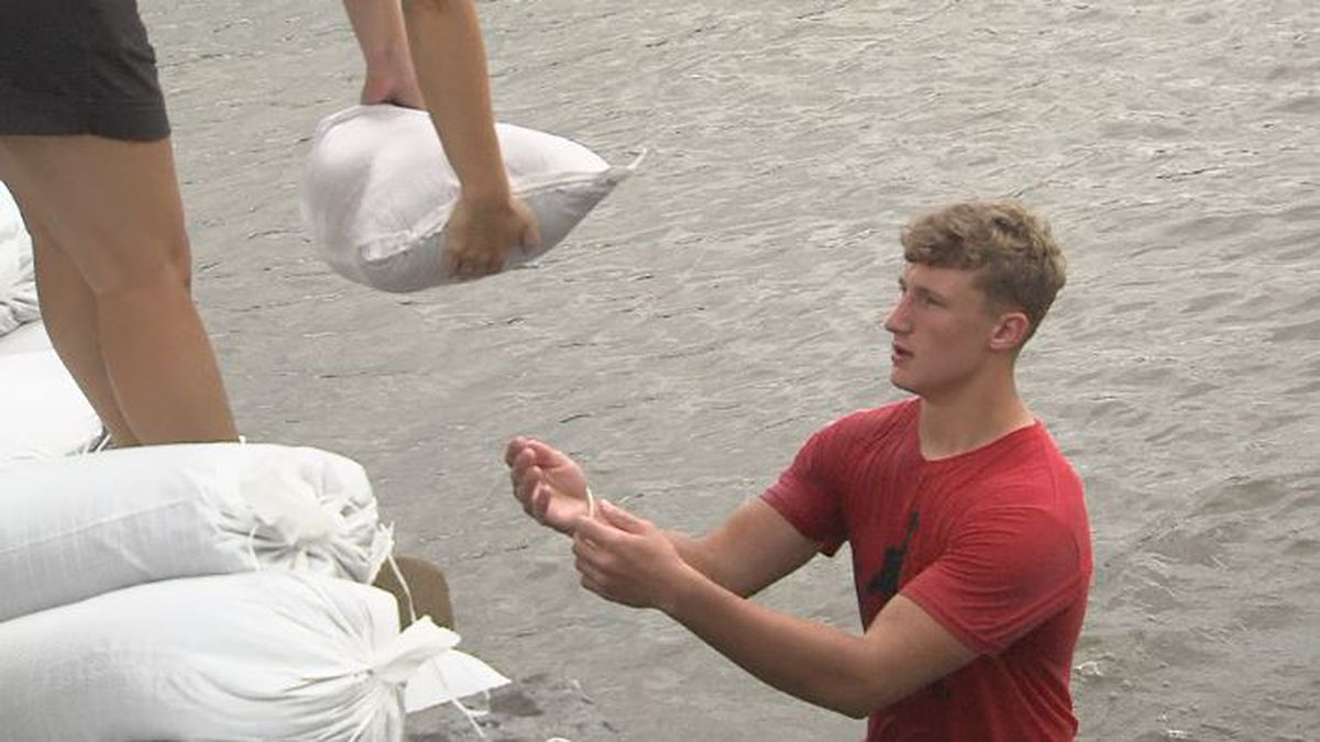 Ayden King carries sandbags to help those affected by the flooding