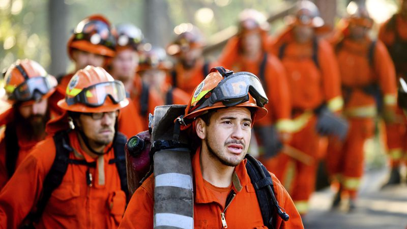In this Oct. 29, 2019, file photo, inmate firefighters prepare to battle the Kincade Fire near...